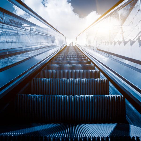Escalator in an underground station with skyline in background.