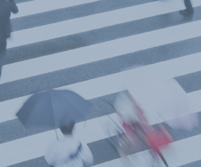 Motion image of people crossing the street on a cloudy day
