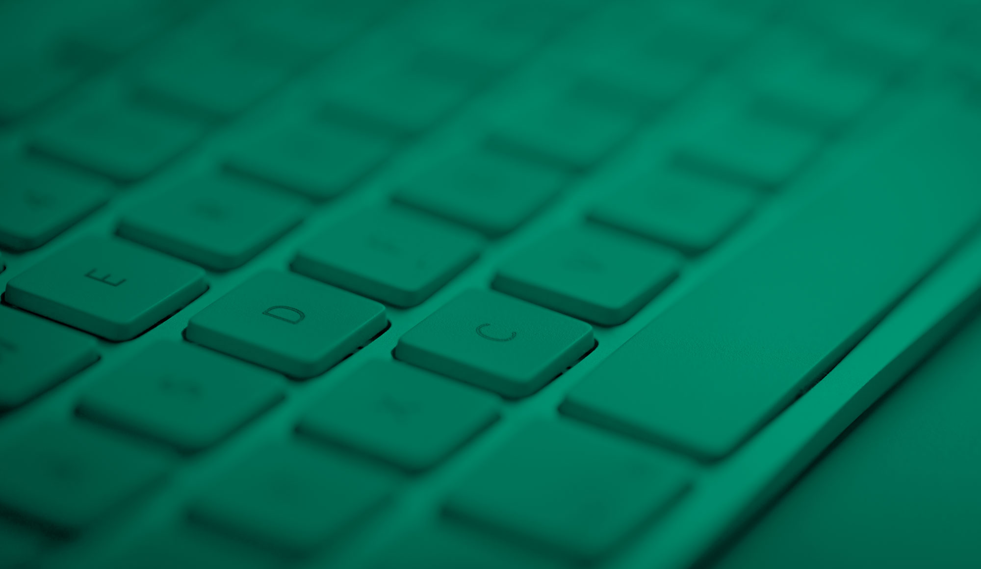 An image of a computer keyboard close-up with green effect
